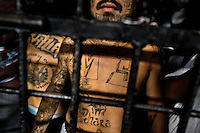 """A member of the Mara Salvatrucha gang (MS-13) stands behind the bars in a cell at the detention center in San Salvador, El Salvador, 20 February 2014. Although the country's two major gangs reached a truce in 2012, the police holding cells currently house more than 3000 inmates, five times more than the official built capacity. Partly because the ordinary Mara gang members did not break with their criminal activities (extortion, street-level distribution of drugs, etc.), partly because Salvadorean police still applies controversial anti-gang law which allows to detain almost anyone for """"suspicion of gang membership"""". Accused young men are held in police detention centers where up to 25 inmates may share a cell of five-by-five metres. Here, in the dark overcrowded cages, under harsh and life-threatening conditions, suspected gang members wait long months, sometimes years, for trial or for to be transported to a regular prison."""