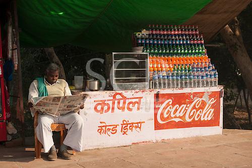 Agra, Utar Pradesh, India. Drinks vendor reading newspaper.