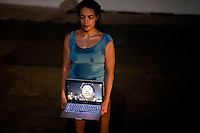 """donna con in mano un computer portatile<br /> Egitto Cairo """"Lessons in revolting"""" at Rawabet Theatre  August 2011`Lessons in Revolting is a performance created by a group of Egyptian activist-artists who want to rewrite their recent history through images, testimonials, scenes and sounds. The performance is directed by Laila Hassan Soleiman and Ruud Gielens with choreography by Karima Mansour."""