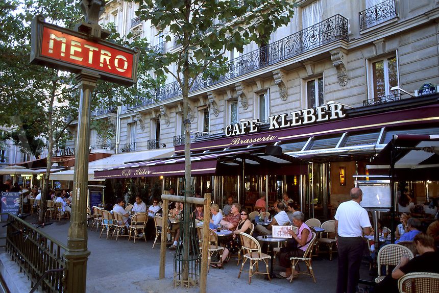 France Life at cafes at the Caf?© Kleber and Metro sign in Paris France
