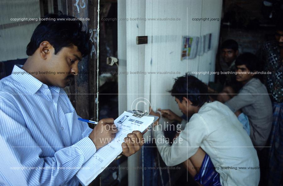 INDIA Uttar Pradesh Mirzapur, Rugmark inspection and certification , worker weaving at carpet loom licensed by Rugmark Foundation to abolish child labour / INDIEN Uttar Pradesh, Rugmark Inspektion und Kontrolle und Zertfizierung in Teppichbetrieb , Teppichknüpfer arbeiten an von Rugmark Stiftung lizensierten Knüpfstuhl in einer Teppichknüpferei in einem Dorf im Teppichgürtel zwischen Badohi und Mirzapur , Rugmark Stiftung kämpft für die Beseitigung von Kinderarbeit