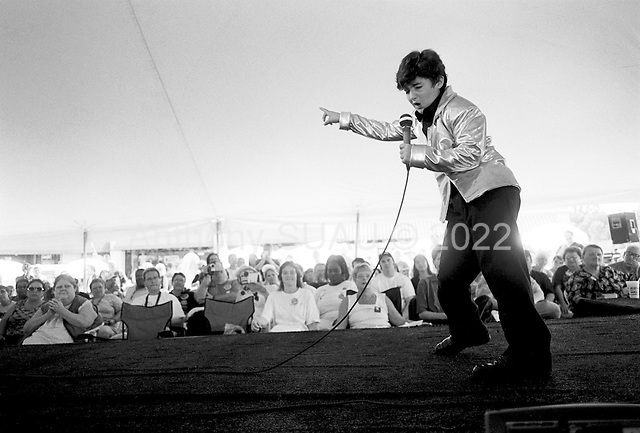 """Memphis, Tennessee<br /> USA<br /> August 14, 2002<br /> <br /> A young boy tells the crowd, """"the more you applaud the more I will shake my hips"""" as he impersonates Elvis during the 25th anniversary of Mr. Presley's death."""