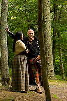 A man and women dressed in Scottish attire talk in the woods during the 52nd Annual Grandfather Mountain Highland Games in Linville, NC.