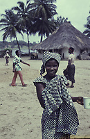 A smiling woman poses for the camera and holds an enamel cup - Half Graway, Maryland County, Liberia, 1979<br /> <br /> In the background palm trees and a traditional hut with a thatched pointed roof