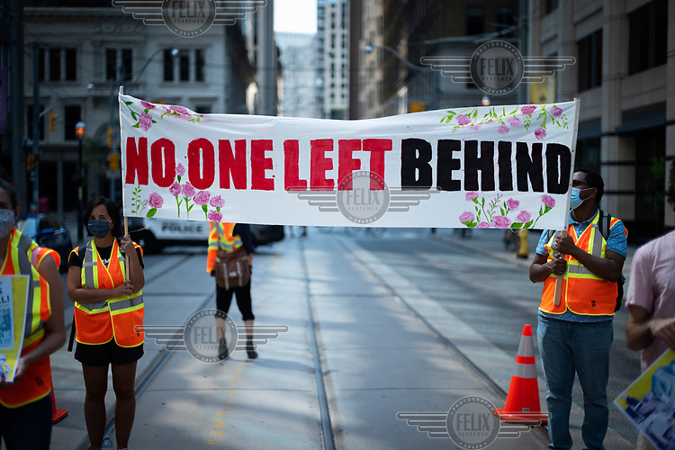 A banner reads: 'No One Left Behond' as the Migrant Workers Alliance for Change stages a demonstration where a human clock reads five minutes to midnight at the The Immigration and Refugee Board of Canada building, at 74 Victoria Street.