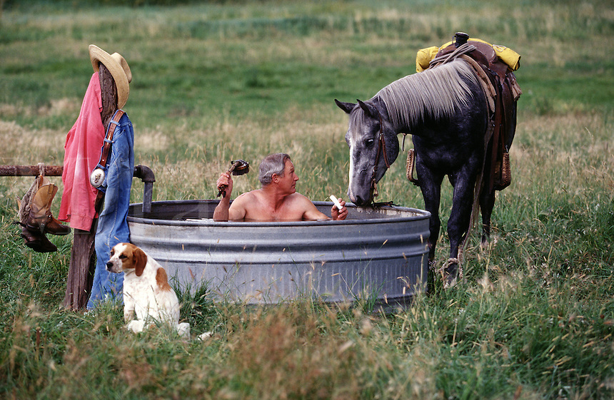 Humorous image of a cowboy taking an outdoors bath accompanied by his dog and horse.
