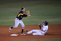Bradenton Marauders second baseman Kevin Kramer (14)  throws to first as Michael O'Neill (12) slides in during a game against the Tampa Yankees on April 11, 2016 at George M. Steinbrenner Field in Tampa, Florida.  Tampa defeated Bradenton 5-2.  (Mike Janes/Four Seam Images)