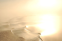 Boat wake curving down the intercoastal waterway near Appalatchicola Florida with fog and sun reflected on the water