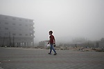 A Palestinian boy carries a teapot and cups on a foggy morning in Gaza city, on August 17, 2020. Photo by Osama Baba