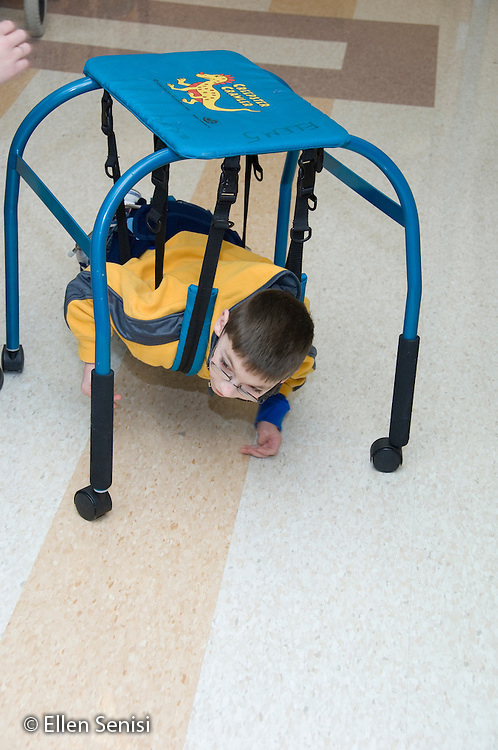 MR / Albany, NY.Langan School at Center for Disability Services .Ungraded private school which serves individuals with multiple disabilities.Child uses a belly crawler as he crawls down the hall. Student is wearing a SWASH (sitting, walking and standing hip apparatus) on his hips / legs. Boy: 9, cerebral palsy, limited verbal output with expressive and receptive language delays.MR: Rub1.© Ellen B. Senisi
