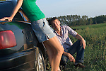 Young couple leaning to car