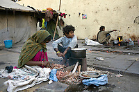 Homeless women and their children cook by the side of the road at a temporary shelter in Karol Bagh, New Delhi.
