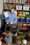 Education Elementary male volunteer reading book to Grade 2 class vertical