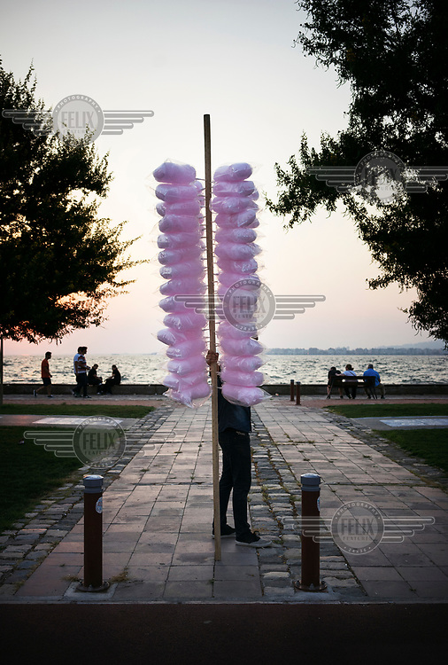 A candy floss seller waits for customers on a seaside promenade.