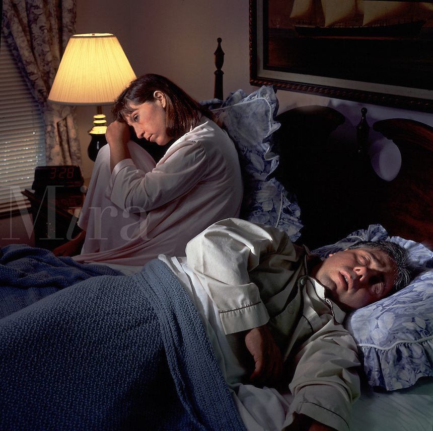 An unhappy woman sits on her bed awake at night as a man sleeps.