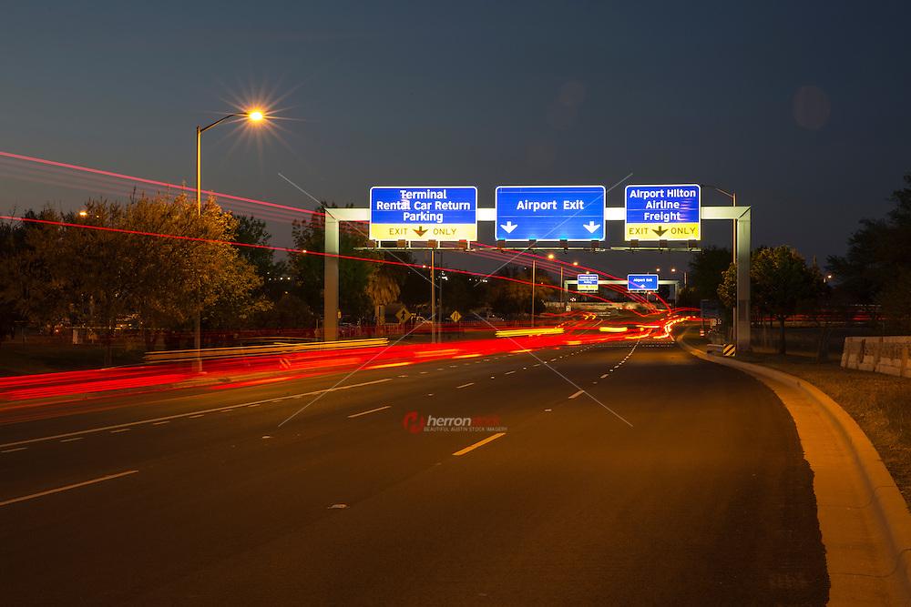 A night time shot of speeding traffic light trails at the Austin–Bergstrom International Airport (ABIA) terminal rental car return exit.