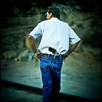 Dick Buck, with a gun tucked into the back of his trousers, walks towards an open train tunnel that crosses between California and Mexico which is commonly thought to be a frequently used passageway for drug smugglers to enter the USA. Mr. Buck owns a ranch less than 5 miles from the border fence. For him the border and everything that comes with it is just a part of life. Although he actively participates in patrolling the area near the fence his main focus is stopping drug smugglers from entering the USA. Like most Minutemen groups in the area, Mr. Buck relays anything he sees to the Border Patrol.