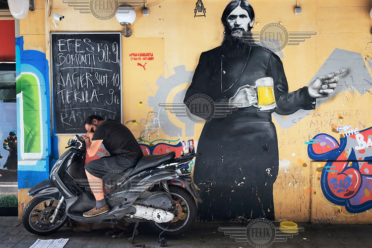 A man sleeping on a scooter parked by a wall decorated with graffiti in Taksim.