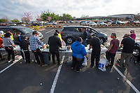 Cars line up to get a free dinner Tuesday April 6, 2021 during a drive through dinner at the Jones Center for Families in Springdale. Chef Rafael Rios of Yeyo's Mexican Grill along with graduates from the Brightwater Center for the Study of Food, Chef Jennyfer Quijada, Chef Jesus Rodriguez and Chef Jose Soto-Rios prepared and served the meals. The event was sponsored by the Jones Center and Civitas, Inc. A total of 300 complimentary meals were served. The menu featured a combination of Mexican and Salvadoran cuisine, including traditional carnitas, Salvadoran curtido, epazote black beans, a variety of specialty salsas and polvorones for dessert. Visit nwaonline.com/210407Daily/ and nwadg.com/photos. (NWA Democrat-Gazette/J.T. Wampler)