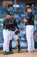 Charlotte Knights pitching coach Richard Dotson (34) has a meeting on the mound with starting pitcher Chris Volstad (44) and catcher Omar Narvaez (14) during the game against the Columbus Clippers at BB&T BallPark on May 3, 2016 in Charlotte, North Carolina.  The Clippers defeated the Knights 8-3.  (Brian Westerholt/Four Seam Images)