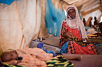 """Fatuma Badel fled Buale, Somalia with 8 children after leaving her sick husband. """"He became sick and I couldn't carry him. I don't know if he is alive or dead. This one, my youngest child was like a dead person when I arrived. Now I thank God I can hear him cry again.""""  Badel has spent 3 days in the Doctors Without Borders hospital with her baby Mohamud who arrived severely malnourished. At nine months old he weighs 4.3 KG. Dadaab refugee camp, Kenya July 22, 2011. Photo: Brendan Bannon"""