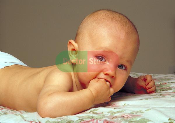baby boy lying on blanket sucking on fingers, teething