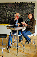 Lifestyle photography of Concord NC, where Elias and Maria Danucalov relax and enjoy an icecream cone inside of the Cabarrus Creamery at 21 Union Street South in downtown Concord, North Carolina. One feature that makes the Cabarrus Creamery special is the local artwork for sale at the front of the store. Photo is part of a photographic series of images featuring Concord, NC, by Charlotte-based photographer Patrick Schneider.