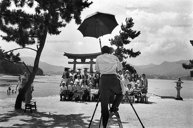 Tourists being photographed by a photographer with the background of Miyajima Torii, floating gate of Itsukushima shrine, Miyajima. It is said that Miyajima is one of the three most beautiful sites in Japan...August 4, 2002.<br /> <br /> Les touristes photographiés par un photographe avec l'arrière-plan de Miyajima Torii, porte flottante du sanctuaire d'Itsukushima, Miyajima. On dit que Miyajima est l'un des trois plus beaux sites du Japon ... le 4 août 2002.