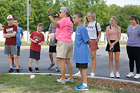 Jannie Layne, president of Bo's Blessings, and Max Williams, youth ambassador, give instructions to volunteers Friday, June 4, 2021, before collecting flags at the National Cemetery in Fayetteville. More than 8,000 flags, provided by the National Cemetery Organization, were posted on the grave sites in recognition of Memorial Day. The flags are dried, rolled up and then stored for future use. Check out nwaonline.com/210605Daily/ and nwadg.com/photos for a photo gallery.<br /> (NWA Democrat-Gazette/David Gottschalk)