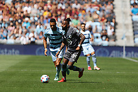 ST. PAUL, MN - AUGUST 21: Romain Metanire #19 of Minnesota United FC with the ball in front of Khiry Shelton #11 of Sporting Kansas City during a game between Sporting Kansas City and Minnesota United FC at Allianz Field on August 21, 2021 in St. Paul, Minnesota.