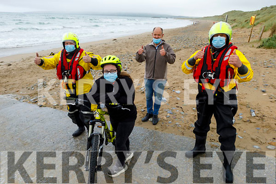 Amber Dunne on her bike at the finish line as Guy Buxton, Richard Hurley and Steve O'Connor from Banna Sea rescue gives her the thumbs up, as she took part in the Virtual Ring of Kerry Charity cycle Finish Line Fantasy Challenge.