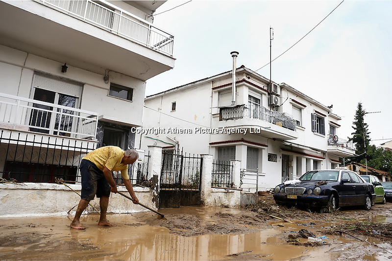 A local man tries to clear mud from outside his house in Agia Triada