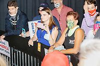 Heather Mullins (in blue), a reporter for the conservative online news outlet Real America's Voice News, which produces former Trump official Steve Bannon's current broadcasting, joins the crowd as people watch from behind the stage barricade as Eric Trump, son of US president Donald Trump, greets people and signs MAGA hats and Trump campaign signs after speaking during a Make America Great Again! campaign rally at the DoubleTree by Hilton Manchester Downtown in Manchester, New Hampshire, on Mon., Oct. 19, 2020.