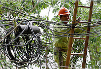 A Chinese worker operates near a tangle of wires in Shanghai, China. China needs to invest 100 billion euros in the next five years to generate enough electricity to meet its huge demand for power and reduce crippling power shortages, state media said. Further investments would be needed, including 75 billion euros to improve power grids..
