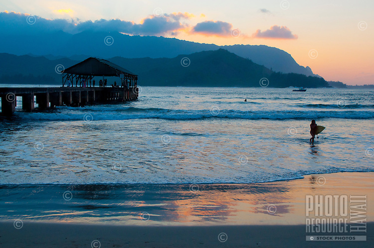 Surfing,swimming, sailing and hanging out on the pier at Hanalei Beach Park on the North Shore of Kauai, with a golden-glow sunset lighting up the water's edge and the sky over Na Pali.