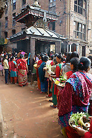 women line up at temple for puja (prayer duty) and offerings, linked to fertility goddess aspects of Durga and her nine incarnations, worshipped in  Dashein festival time in Newar city Bhaktapur in Kathmandu valley, Nepal, October 2011. The first day of dashain, barley seeds are sewn, growing  quickly to be carried at the end of the festival  to the temple as part of the offerings.Offerings on the plate also contain  other symbols of fertility, like egg, fruits, flowers, herbs.