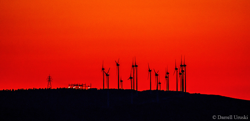 Fine Art Landscape Photograph. Captured along the  coastline of Greece. Spectacular red sunset scene of wind turbines set upon the top of the hillside and silhouetted against the red evening sky.