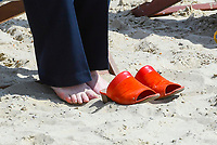 BNPS.co.uk (01202 558833)<br /> Pic: Graham Hunt/BNPS<br /> <br /> A councillor takes her shoes off during the meeting.<br /> <br /> Town hall officials swapped their stuffy chambers for the sand and sea today as they took part in what is thought to be the UK's first ever council meeting on a beach.<br /> <br /> Weymouth Town Council in Dorset held the event on the beach in protest at the Government banning virtual meetings.<br /> <br /> Since May 6, votes cast at virtual council meetings have not been legally binding following a controversial ruling upheld by a High Court judge.<br /> <br /> But because social distancing is difficult to practice in many town halls, officials in Weymouth used a loophole in the rules to meet on a beach.