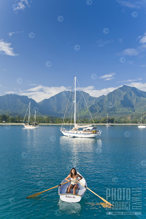 Asian woman rowing a dinghy in Hanalei Bay with Namolokama Mountain in the background
