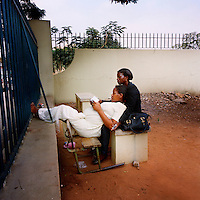 Two students, one of whom is pregnant, take a rest on a bench outside the main building of the Agostinho Neto University literature faculty.