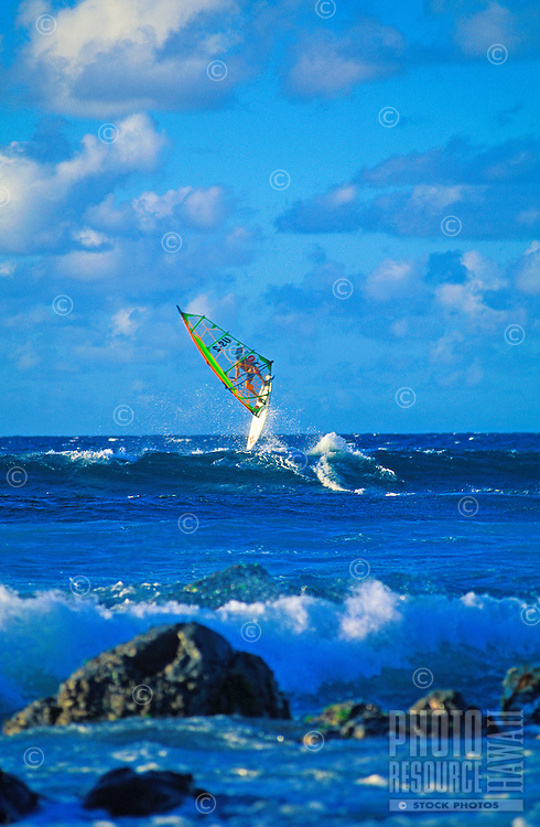 A windsurfer at Hookipa Beach Park balances on wave. Maui's best and most popular beach park for surfing and windsurfing is just outside the town of Paia on the Hana Highway. Ho'okipa means hospitality in Hawaiian.