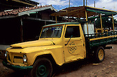 "Macapa, Amazon, Brazil. Battered yellow pickup truck with a roof over the back, with  ""Brasil 1996 Ouro"" logo, with the Olympic rings on the door."