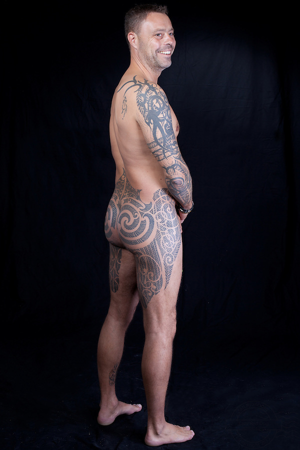 Danish man, with extensive tattoos on lower back, thighs, hips and right arm. Tribal style.<br /> From the Kolding Tattoo Convention, Denmark