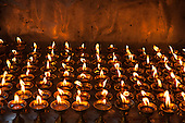 Dharamsala, Himachal Pradesh, India. Rows of burning butter lamps at the Buddhist temple in the Norbulingka Institute.