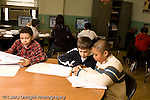Education Elementary school mixed ages afterschool program for intellectually gifted students  male students doing work on paper at table other students in background using computers horizontal