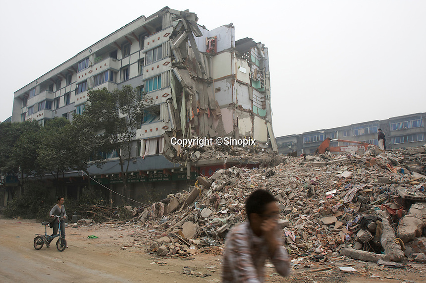 People pass by the collapsed buildings in Dujiangyan, Sichuan, China. The earthquake happened at 14:28pm on 12 May 2008, with the epicenter in Wenchuan County, about 159km NW of Chengdu, Sichuan, China..17 May 2008