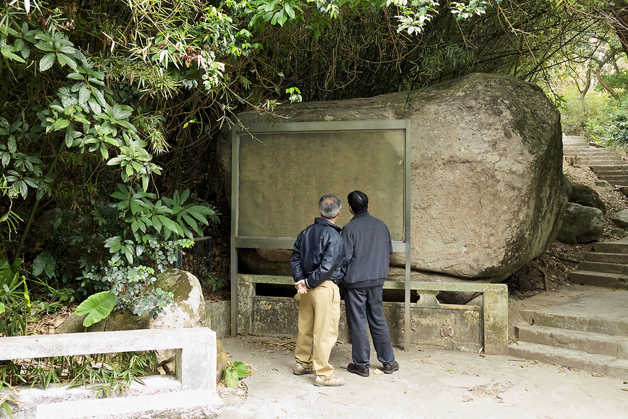 Two walkers inspect the rock inscription at Joss House Bay (Tei Tong Tsui) from 1274.  The protective panel has since been removed.