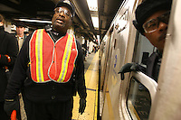 """NYC transit worker Kenneth Hoyt does 'platform control' during rush hour on the uptown Lexington Ave. line at the Grand Central subway station on the same day that the contract between the Transit Worker's Union (TWU) and the NYC Metropolitan Transportation Authority (MTA) expired on Friday, December 16, 2005.  The TWU's leadership has decided to continue with contract negotiations for at least another four days before declaring a strike, and Hoyt, a subway conductor who has been with the MTA for 36 years, said he hopes the union doesn't """"give in."""""""