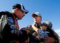 Sept. 6, 2010; Clermont, IN, USA; NHRA top fuel dragster driver Larry Dixon holds his daughter as he is congratulated by Cory McClenathan after winning the U.S. Nationals at O'Reilly Raceway Park at Indianapolis. Mandatory Credit: Mark J. Rebilas-