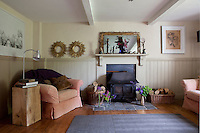 A wood burning stove is situated between a pair of log baskets in this bright living room